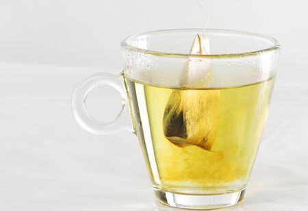 Closeup of a tea bag in a glass cup full of water with beautiful yellow color effects in the transparency of the water