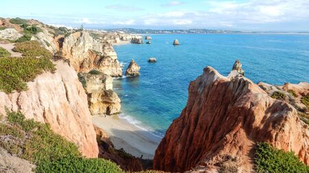 Panoramic view of the ocean cliffs of the Algarve, Portugal, with cloudy blue sky