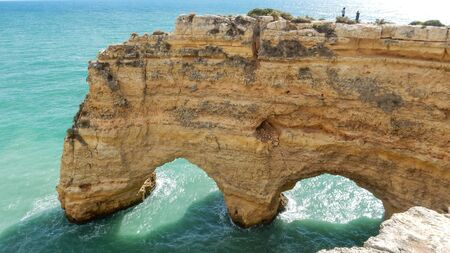 Panoramic view of the ocean cliffs of the Algarve, Portugal, with orange rocks on the blue sea