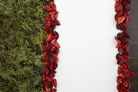 Flat lay Christmas copy space with pine branches on one side and red petals bordering a white background Standard-Bild
