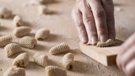 Close up process of homemade vegan gnocchi pasta with wholemeal flour making. The home cook crawls on the special wooden tool the gnocco , traditional Italian pasta, woman cooks food in the kitchen