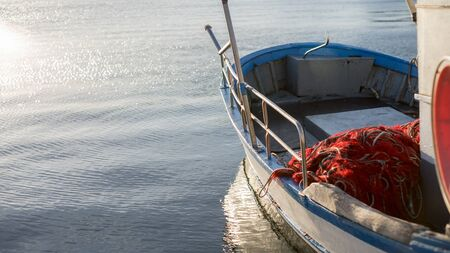 A moored fishing boat is lulled by the water while the sun reflects on the sea early in the morning with the winch of the fishing net in the foreground