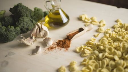Close-up of typical Italian Apulian fresh pasta orecchiette on a table with broccoli, garlic, oil and chilli powder - log prores