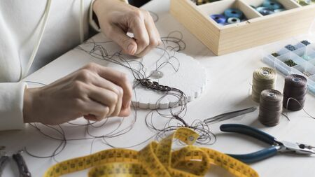 Lifestyle concept, work from home to reinvent your life: close-up of woman hands making macrame knotted jewelry with stone beads and tools on light wooden table 免版税图像