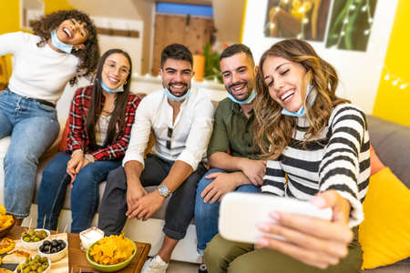 Group of mixed race friends making selfie celebrating at home with medical protection mask