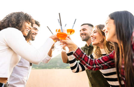 Mixed race happy friends group toasting with spritz glasses outdoor at sunset - Young people having fun together drinking cocktail for aperitif time - Bright vivid filter with focus on bearded men