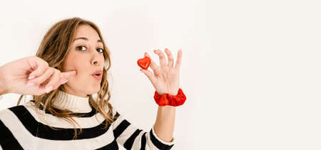 Head and shoulders close up of a blonde cute excited woman looking at the camera holding a heart-shaped chocolate between your fingers and gluttony expression - Chocolate: symbol of sin and temptation