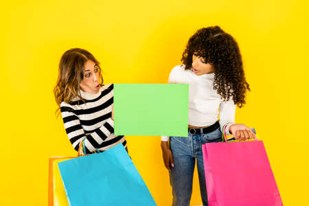 Colors and fun for shopping - Two beautiful young women look at an empty sign that I hold in my hand, ideal as a copy space - Multiracial female models excited and surprised holding some shopping bags