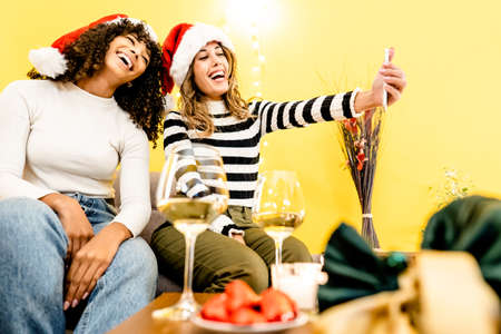 Family holidays with diversity: beautiful blonde takes a selfie at home with her black Hispanic girlfriend wearing Santa hat - Modern people different relationships and habits with technology