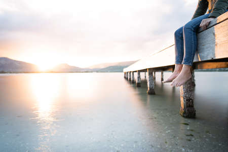 Alone unrecognizable female person sitting on a wooden pier at sunset or dawn with feet dangling on the water - Pensive woman with winter dress admires the sun going down in the evening on the water