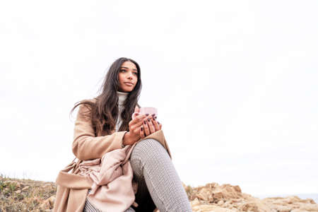 Glamour picture of a beautiful black Hispanic long hair woman sitting on a sea rock holding a mug looking at horizon - Pensive cute stylish female person view from bottom with large white copy space Stok Fotoğraf