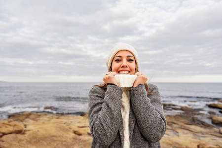 Beautiful young Caucasian woman tightens the neck of her white sweater with her hands for the cold winter weather smiling looking at the camera on sea rocks of Sardinia vacation resort with cloudy sky