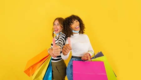 Two confident mixed-race young women holding colored shopping bags and smiling doing thumbs up looking at the camera on big yellow background copy space, wearing Coronavirus protection mask 스톡 콘텐츠