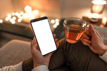 New reading technology using smartphone to enjoying preferred ebook: close up of unrecognizable woman sitting on sofa holding a cup of tea in one hand and big display cell phone with blank white screen