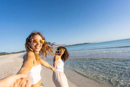 Two young beautiful girls with colorful sunglasses dress boho in summer looking at camera on the beach laughing amused for happiness on vacation pulling hand of the photographer in follow me gesture Reklamní fotografie