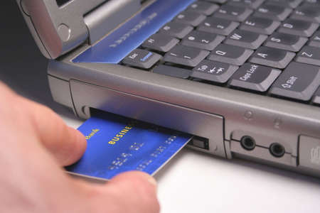 debit card: Sliding a debit card directly into a computer.