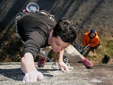 tenacity: A rock climber struggles to hold on. Stock Photo