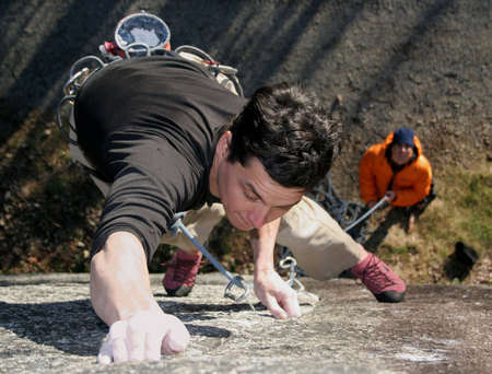 A rock climber struggles to hold on. Banque d'images