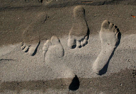A pair of lovers  footprints marks their passing until the next wave erases them.