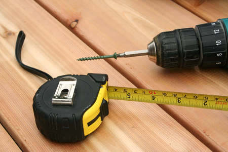A drill and a tape measure on a new deck. Stock Photo - 440200