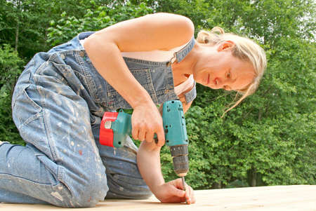 An attractive woman renovates the deck of her new home. Stock Photo - 440197