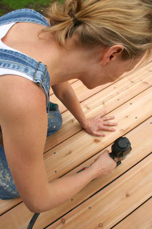 doityourself: A girl uses an air gun to nail her new deck.