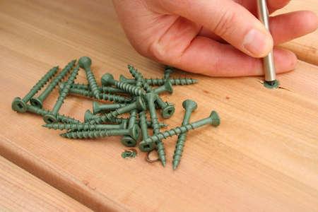 Screwing on new cedar decking. Stock Photo - 440142