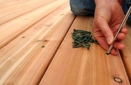 A hanywoman screws on new cedar decking.  Copy space on left.