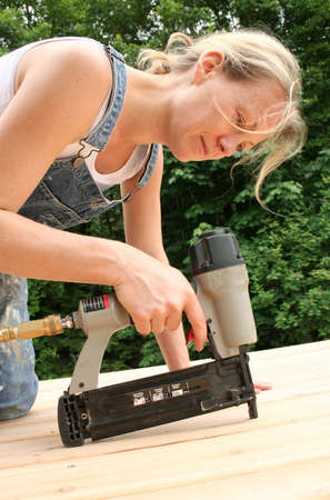 handywoman: An attractive girl shows off her handywoman skills by nailing on new cedar decking. Stock Photo