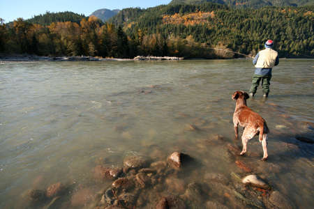 dog salmon: A fisherman and his dog wait patiently for the salmon to bite. Stock Photo