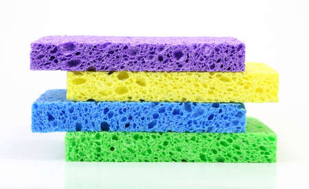 A stack of four colorful cleaning sponges against a white background.