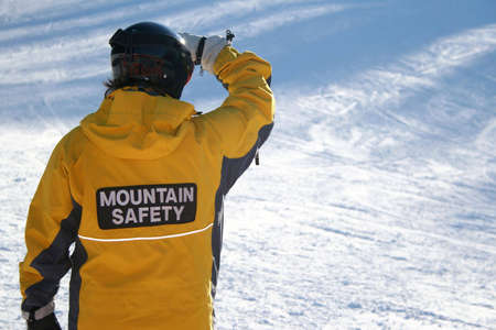 ensures: A worker at a ski hill ensures the safety of its winter visitors. Stock Photo
