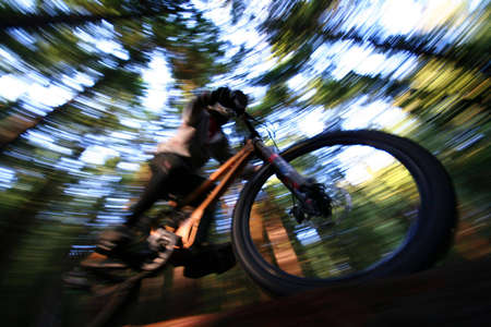 girl on bike: A heavily blurred mountain biker on a trail in Vancouvers famous North Shore mountains.