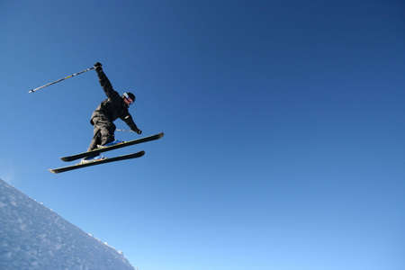 A skier in a business-like pinstripe ski suit flies through the air.