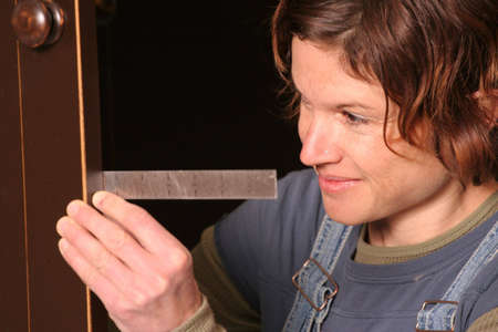 A woodworker smiles as she checks the fit of a cabinet door. Imagens