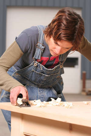 A female woodworker planes the top of a new table. Stock fotó