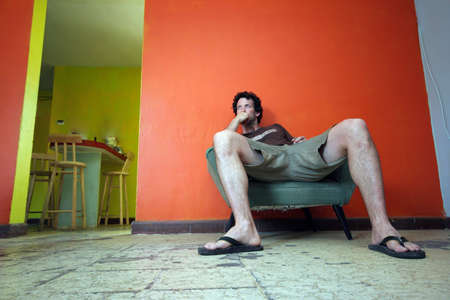 A man sits on a weathered chair in a room in Mexico. Stok Fotoğraf
