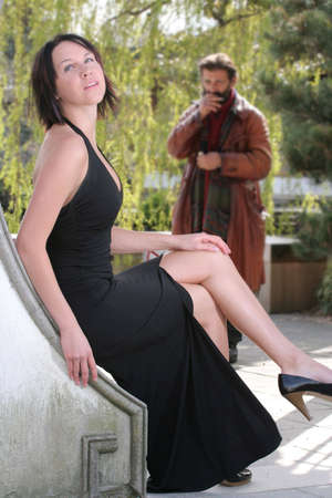 admirer: A young woman sits and waits while an admirer (unrecognizable and heavily blurred) watches in the background. Stock Photo