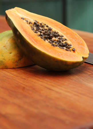 A ripe papaya cut in half on a wooden chop block. Stock fotó