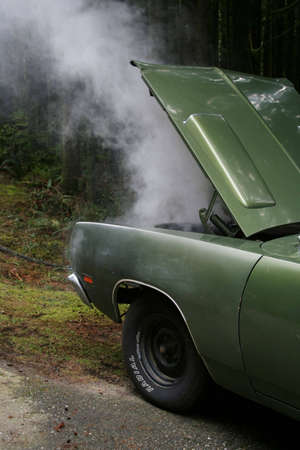 coolant: A car steams from overheating on the side of the road.