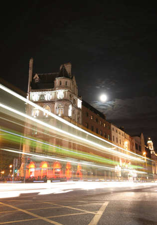 A long exposure photo of traffic passing a building in historic Dublin.