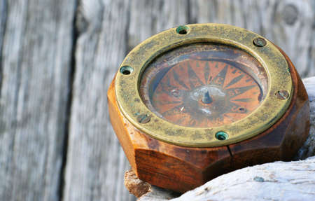 A vintage compass sits on a weathered wood background.