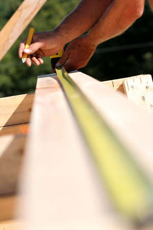 A carpenter measures a piece of lumber for a new home.