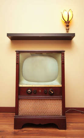 A retro TV sits below a shelf and a tulip lamp.