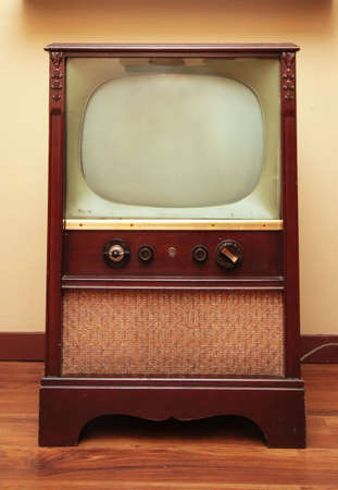 An old retro television with a small screen and a big speaker.