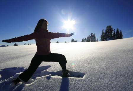 astral body: Una mujer golpea el guerrero yoga mientras que plantean en un prado cubierto de nieve.