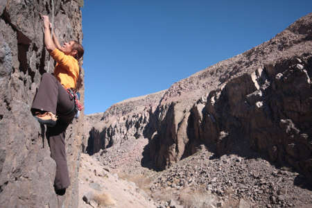 A woman makes her way up a challenging rock face.