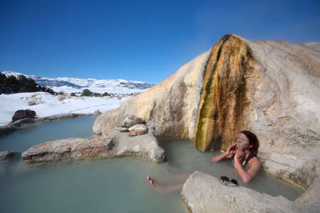 A woman applies mud to her face in a natural hot spring pool in California.