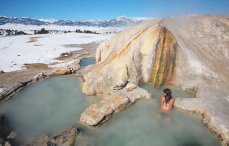 A girl relaxes in the pool of a natural hot spring.