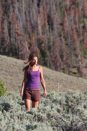 mountin: A naturally beautiful girl walking through a meadow of sage near Rocky Mountin National Park, Colorado. Stock Photo